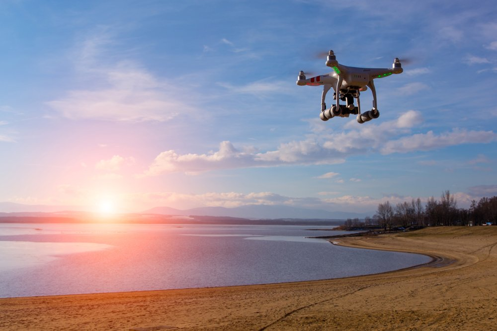 Image of a drone flying along a beach at sunset