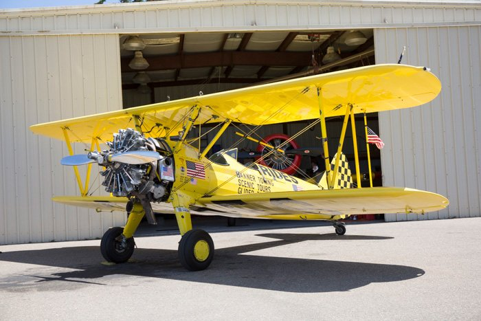Yellow bi plane parked in front of a hangar