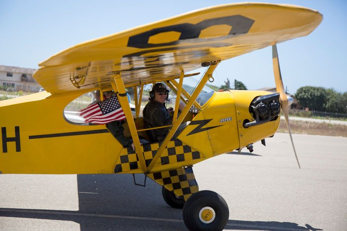 Close up photo of a small yellow taildragger airplane taxing