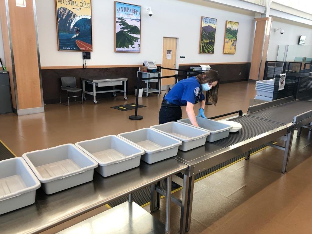 TSA Officer Cleaning Bins